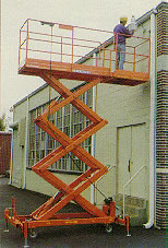 Photo of worker on raised Scissor Lift with a 3 by 3 cantilever